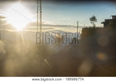 Sun rise behind Himalayan Mountains - shot from inside of a glass window using light flares and colours capturing the beauty of cold environment. At Sikkim India.