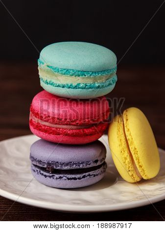 Colorful macaroons on white plate on dark wooden background. Macaroons close up
