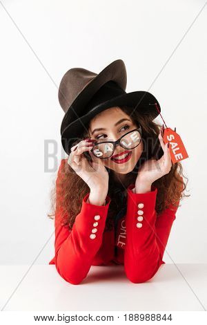 Picture of smiling young caucasian lady sitting isolated over white background wearing a lot of hats by sale. Looking aside.