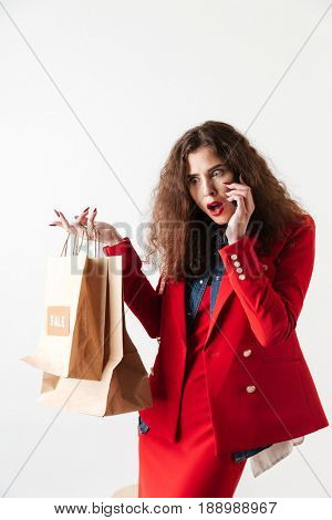 Surprised astonished sale woman talking on mobile phone and holding paper shopping bags isolated over white background