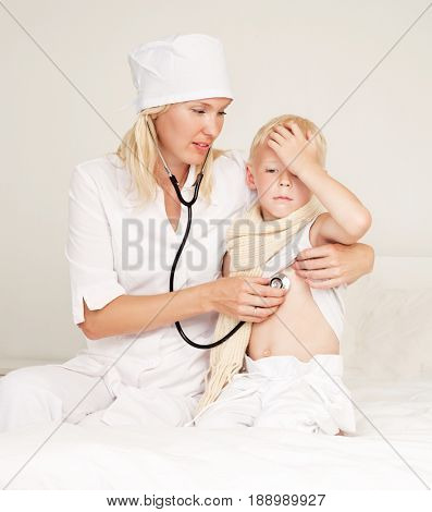 doctor examining a child with phonendoscope in bed at home
