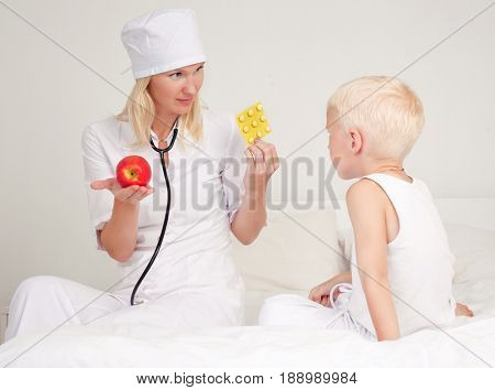 doctor giving a child apple and pills in bed at home