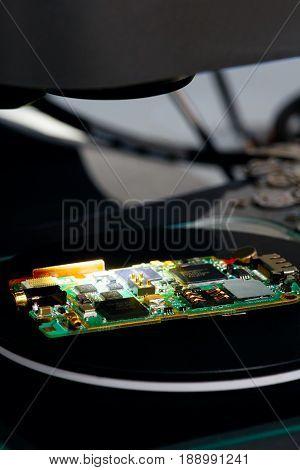 Nano technology concept background. Micro chip matrix illuminated on a microscope table