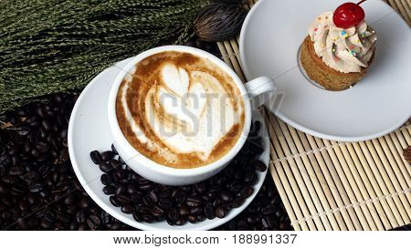 Hot cappuccino or latte art coffee and cake with a cherry. A cup of coffee on the wooden table with dark roasted coffee beans. Morning breakfast with coffee. Flower shape created by milk.