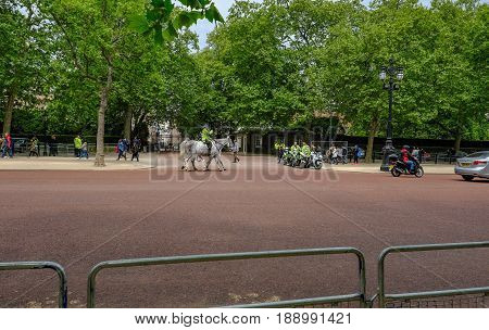 London UK - May 11 2017: Metropolitan Police on horseback and motorbikes outside royal residence in The Mall. Railings and road in the foreground.