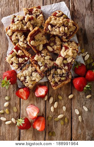 Homemade Strawberry Bars With Oatmeal, Peanuts And Pumpkin Seeds Close-up. Vertical Top View
