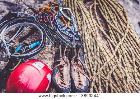Rock climbing equipment including rope, shoes, helmet and snap hooks.