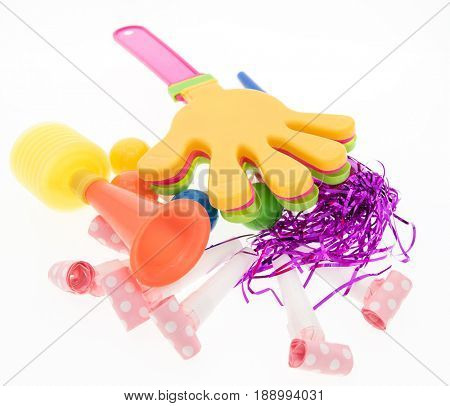 Party horn and noisy toy-rattle in the form of palm on white background