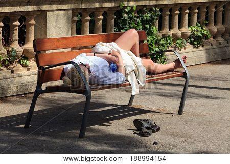 April 16, 2013 Spain, Barcelona, a woman sleeping on a bench