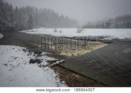 Landscape With A River And Its Banks Covered With Fluffy Snow During Weather Phenomena - Snowfall In