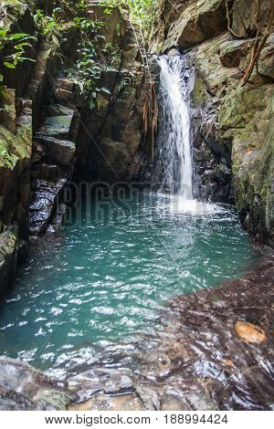 Closeup image of waterfall and small lake in the rocks of the rain forest of Khao Sok sanctuary Thailand