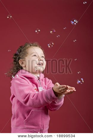 Little girl catching soap bubbles