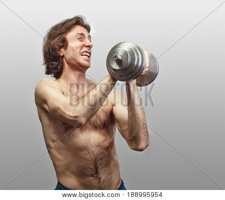 weak man trying lift up heavy dumbbell isolate on studio background