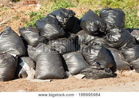 Pile of household waste in black garbage bags dumped at roadside