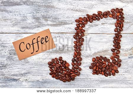 Tune from coffee beans, message. Coffee beans melody, wooden background.
