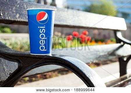 Minsk, Belarus, may 19, 2017: paper cup of Pepsi on a bench in the city on a blurry background of red flowers in the color of the logo Pepsi
