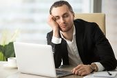 Young man dozing with head on hand while sitting at desk with laptop in office. Businessman sleeping at workplace in morning after weekend party day before. Tired male entrepreneur slumbers at work poster