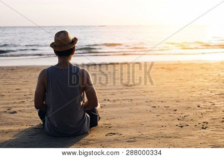 Young Male Travel Backpacker Practicing Zen Meditation On Outdoors Tropical Sea Beach On Silhouette