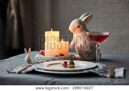 Selective Focus Of Plates With Eggs, Wine In Crystal Glass, Burning Candles And Decorative Bunnies O