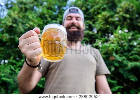 Cheers concept. Distinct beer culture. Hipster brutal bearded man hold mug cold fresh beer. Man relaxing enjoying beer in summer. Alcohol drink and bar. Craft beer is young, urban and fashionable poster