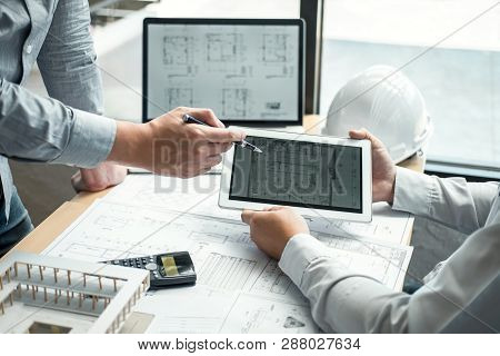 Construction Engineering Or Architect Discussing A Blueprint And Building Model While Checking Infor