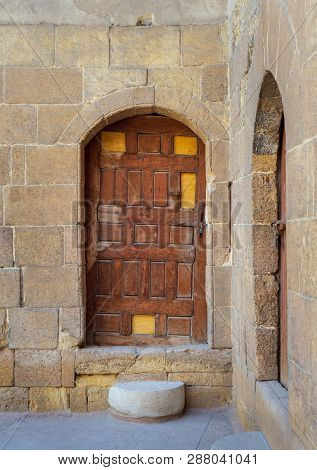 Cairo, Egypt - December 2 2018: Old Wooden Door Framed By Arched Bricks Stone Wall At The Courtyard