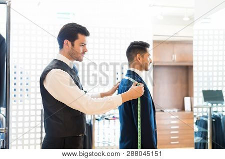 Side View Of Clothier Measuring Back Width Of His Client With Tape Measure In Store