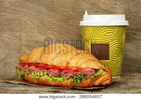Big Croissant With Green Salad, Tomatoes And Pork Meat Near Paper Coffee Cup On Old Wooden Backgroun