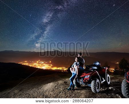 Active Man And Woman Trevelers With Atv Quad Motorbike On The Top Of Mountain, Romantic Couple Enjoy