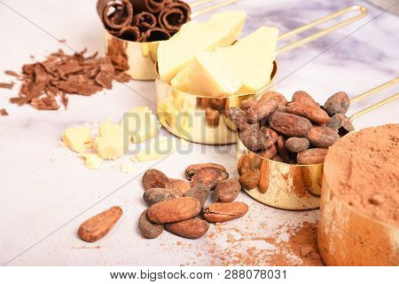 Cocoa, Cocoa Butter And Cocoa Beans, Chocolate In Gold Containers On A Marble Surface. Flat Lay. Pla