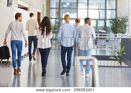 Group of students in college walk in university hallway