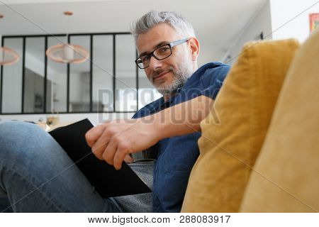 Man in 40s reading book in modern home poster