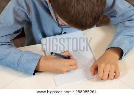 Boy Sits At A Desk With A Pen In His Hand And Writes In A Notebook.