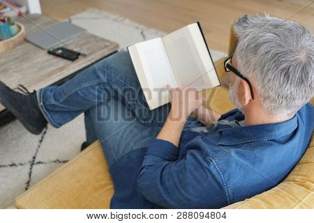 Man in 40s reading book in modern home