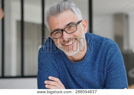 Portrait of smiling man with grey hair and glasses