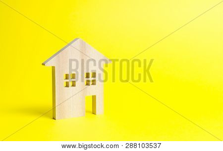 Wooden Residential House On A Yellow Background. Mortgage And Credit For The Purchase. Minimalism. I