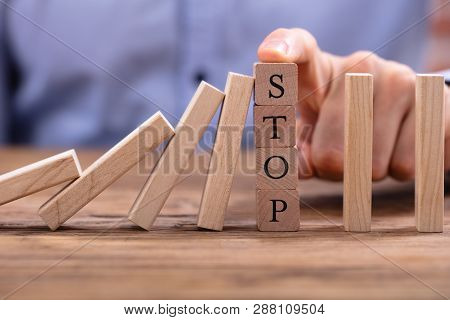 Wooden Blocks With Stop Text Stopping Falling Dominos