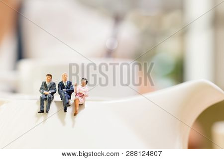 Miniature People : Businessman And Woman Sitting On A Cup Of Tea And Copy Space For Text