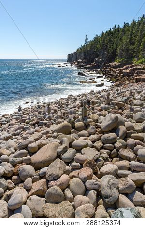 Boulder beach, Acadia National Park, Maine. A clear summer day with calm seas. Tourist have stacked some of the boulders to make towers.