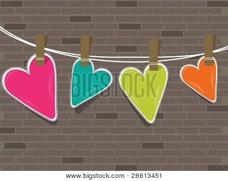 Colorful hearts hanging on a line against wall  for valentine day and other occasions.