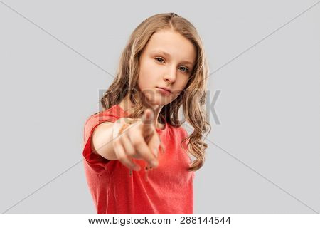 accusing gesture and people concept - teenage girl with long hair in red t-shirt pointing finger to you over grey background