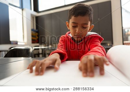 Front view of cute blind mixed-race schoolboy reading a braille book at desk in a classroom at elementary school