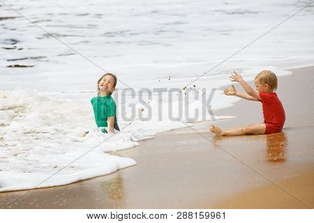 Brother And Sister Playing With Sand And Water On A Tropical Beach, Dressed In Protective Wetsuit. T