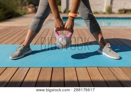 Low section of African American woman exercising with kettlebell next to the swimming pool in the backyard of home on a sunny day