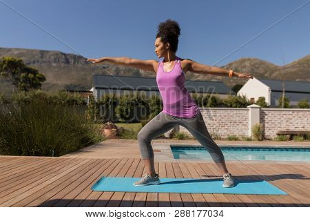 Front view of a young African American woman performing stretching exercise next to the swimming pool in the backyard of home on a sunny day
