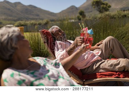 Side view of an active African American senior couple toasting glasses of cocktail while relaxing in the lounger chairs in the backyard of home