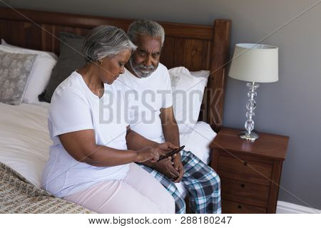 Side view of a senior African American couple using mobile phone in bedroom at home