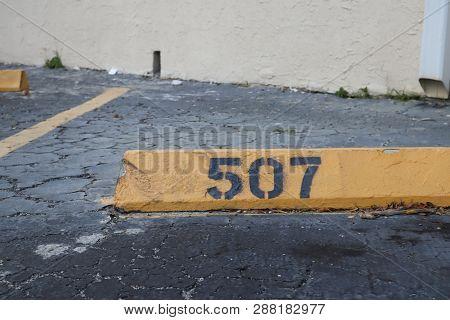 Number 507 Black On Yellow. Asphalt On The Background. Black Number Stencil Painted On Backdrop, Num