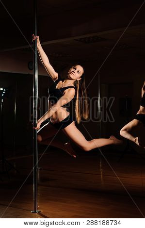 Beautiful Slim Girl With Pylon. Female Pole Dancer Woman Dancing On A Pole On A Black Background