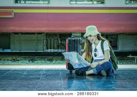 Asia Woman Traveller Sitting And Looking At The Map Before Go To Travel At The Train Station, Travel